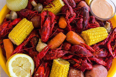 tray full of cooked crawfish with corn, carrots, mushrooms and dip, how to boil crawfish, crawfish boil,