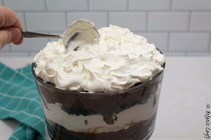 trifle almost finished, cool whip being added on the top with a spoon