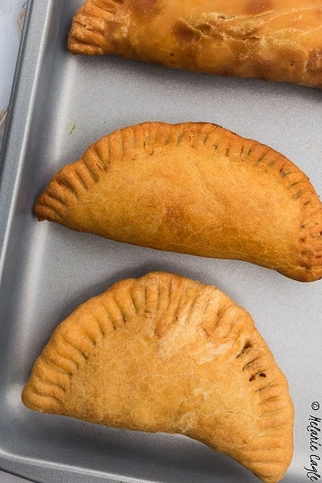 meat pies arranged on a baking tray