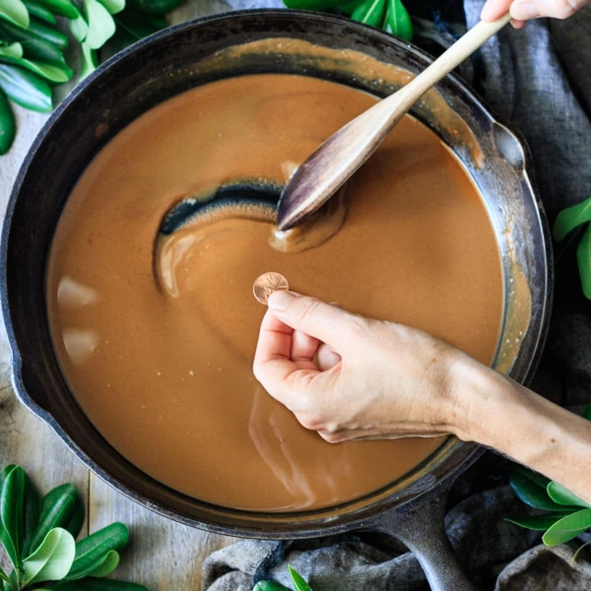 making a roux in a cast iron pot with a hand showing the color against a penny