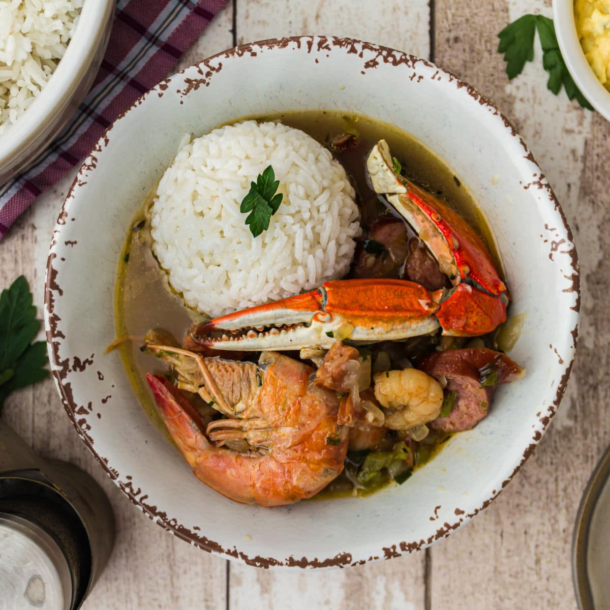overhead shot of a bowl of seafood gumbo with a scoop of rice