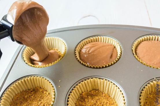 s'mores cupcakes having batter poured onto graham cracker crust