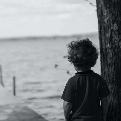 boy leaning against tree signs of autism