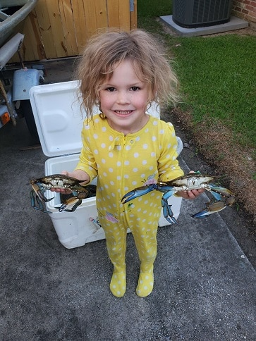 little girl in yellow pyjamas with wild hair holding some blue crabs from an ice chest