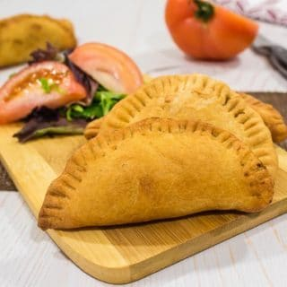 meat pies lying on chopping board with salad