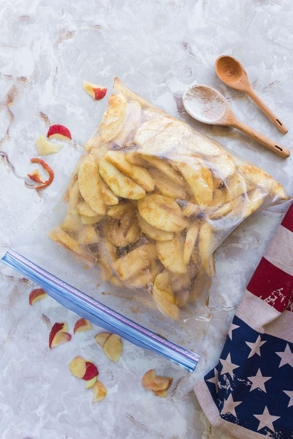 ziplok bad filled with apple slices, cinnamon, sugar and flour.  With an american flag and two wooden spoons