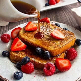 Syrup being poured onto two slices of french bread with strawberries, raspberries and blueberries