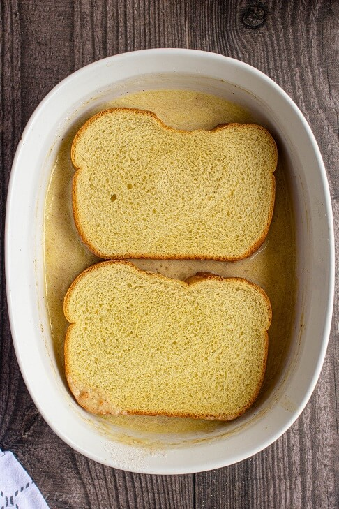 two pieces of brioche bread soaking up egg batter