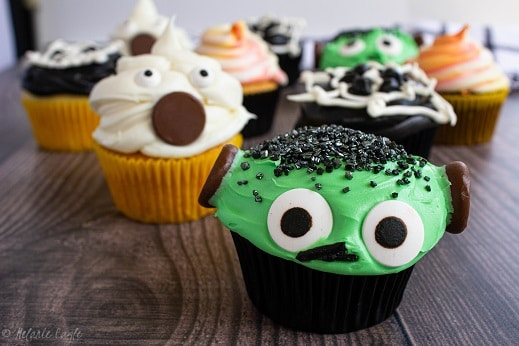 halloween cupcakes with frankenstein green in front, a white ghost behind and a spider web cupcake