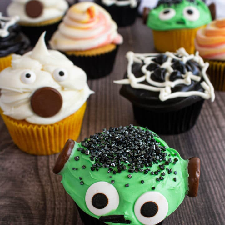 close up of halloween cupcakes, with ghost cupcake, frankenstein cupcake, spiderweb cupcake