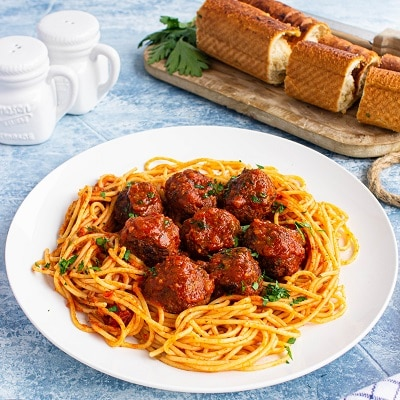 plate of spaghetti topped with meatballs with a garlic loaf in the back