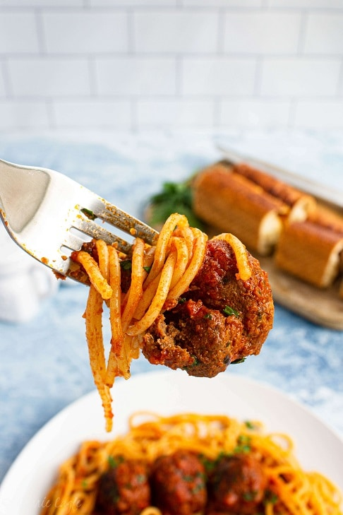 spaghetti and meatballs coming toward the mouth with bread in the background