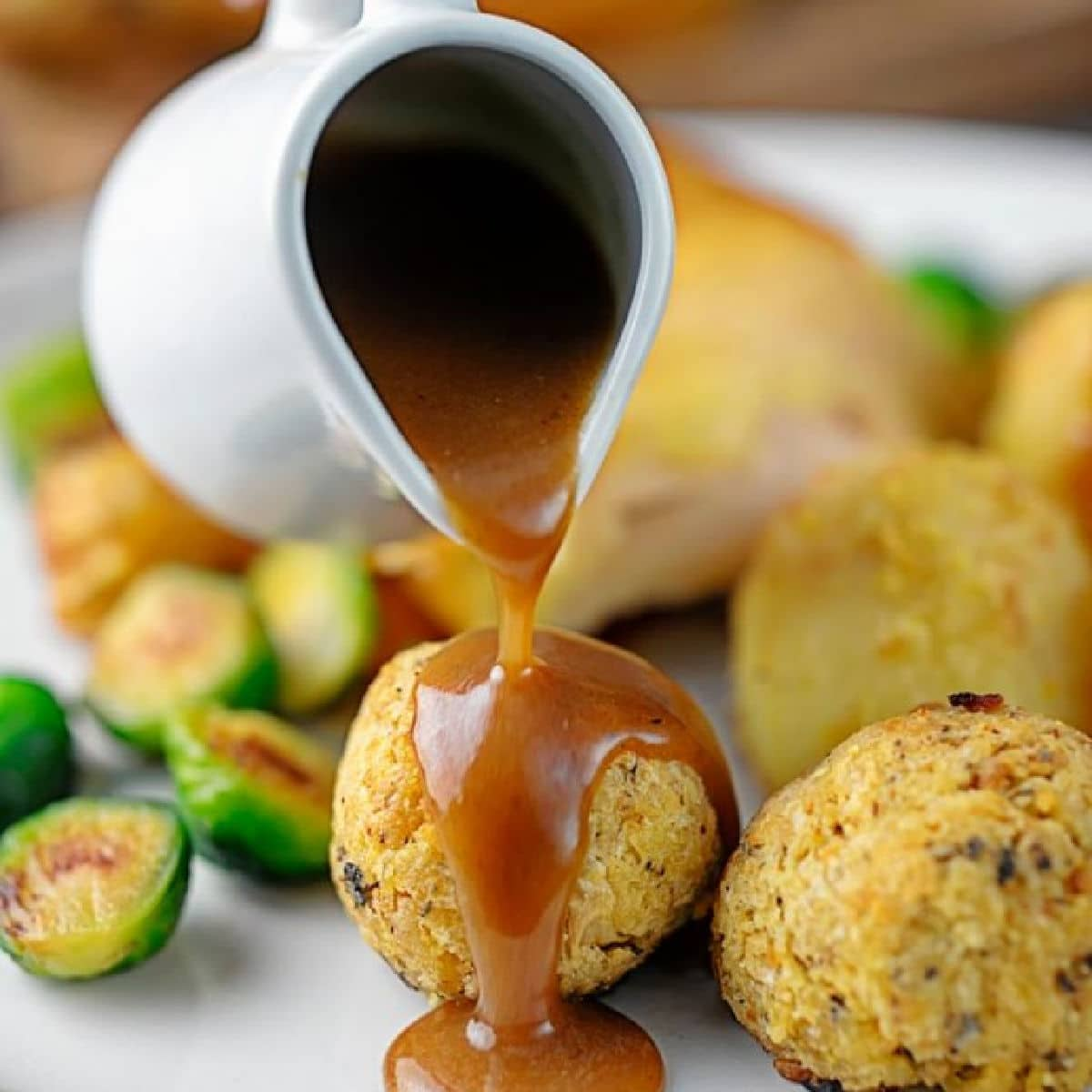 gravy being poured onto a stuffing ball