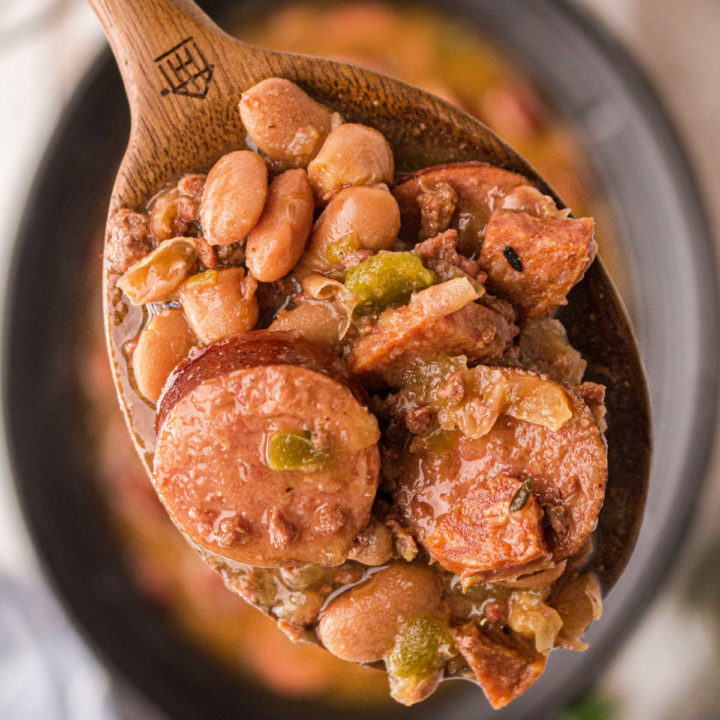 close up of some pinto beans and sausage on a spoon over a crock pot