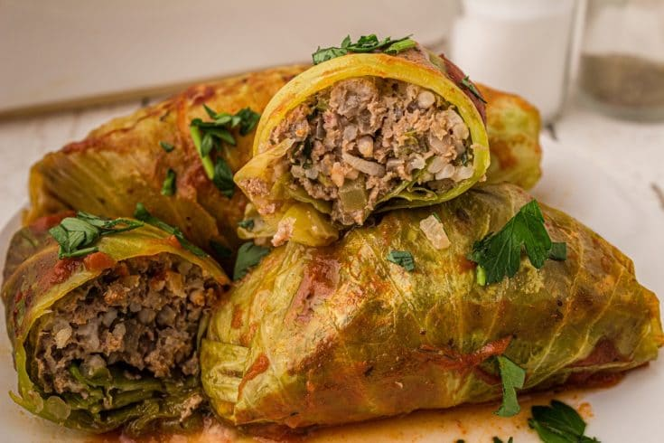 cabbage rolls in pile with one sliced open showing the stuffed meat inside