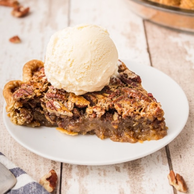 A slice of pecan pie with a round of ice cream on top