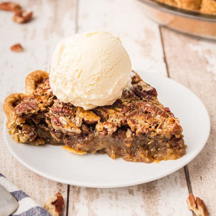 a plate with a slice of pecan pie with a ball of ice cream sitting on top