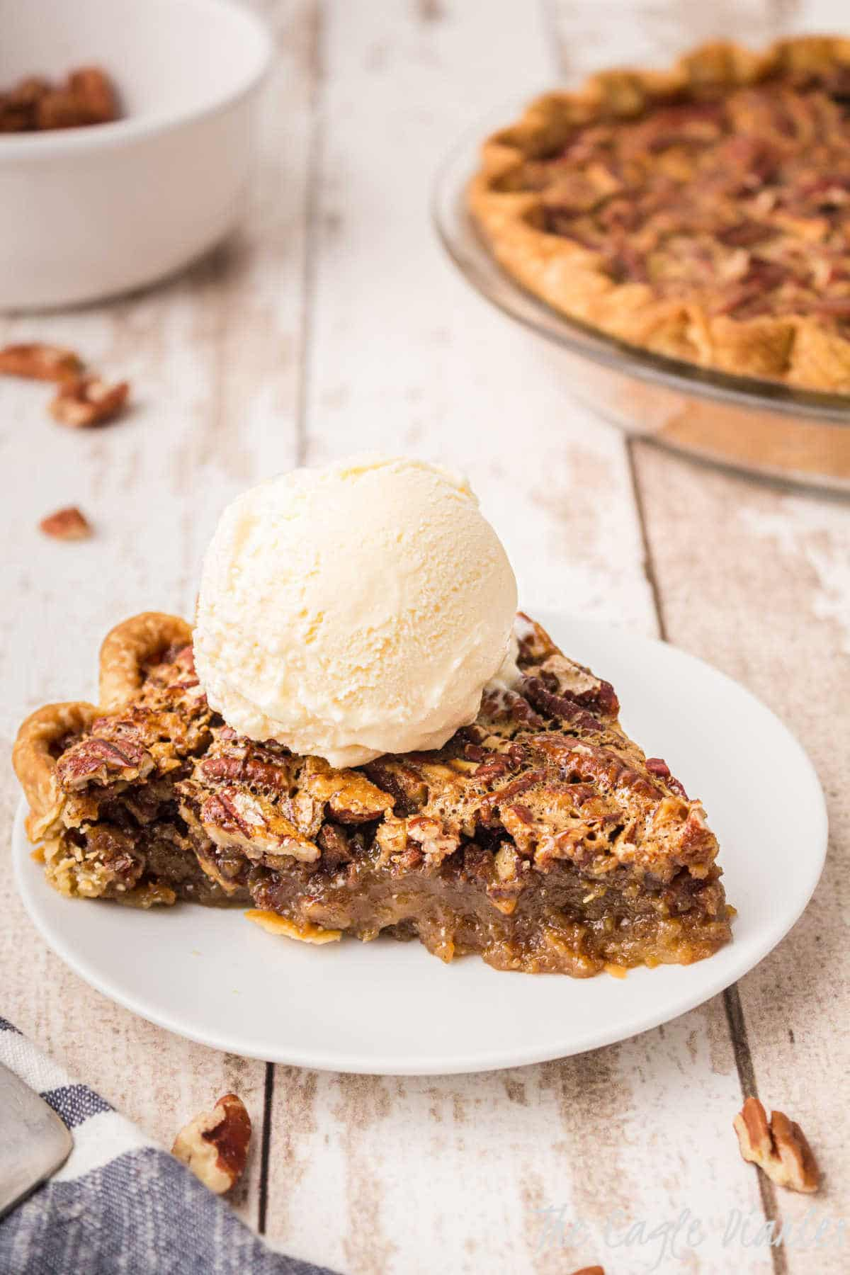 a piece of pecan pie with a scoop of ice cream on top