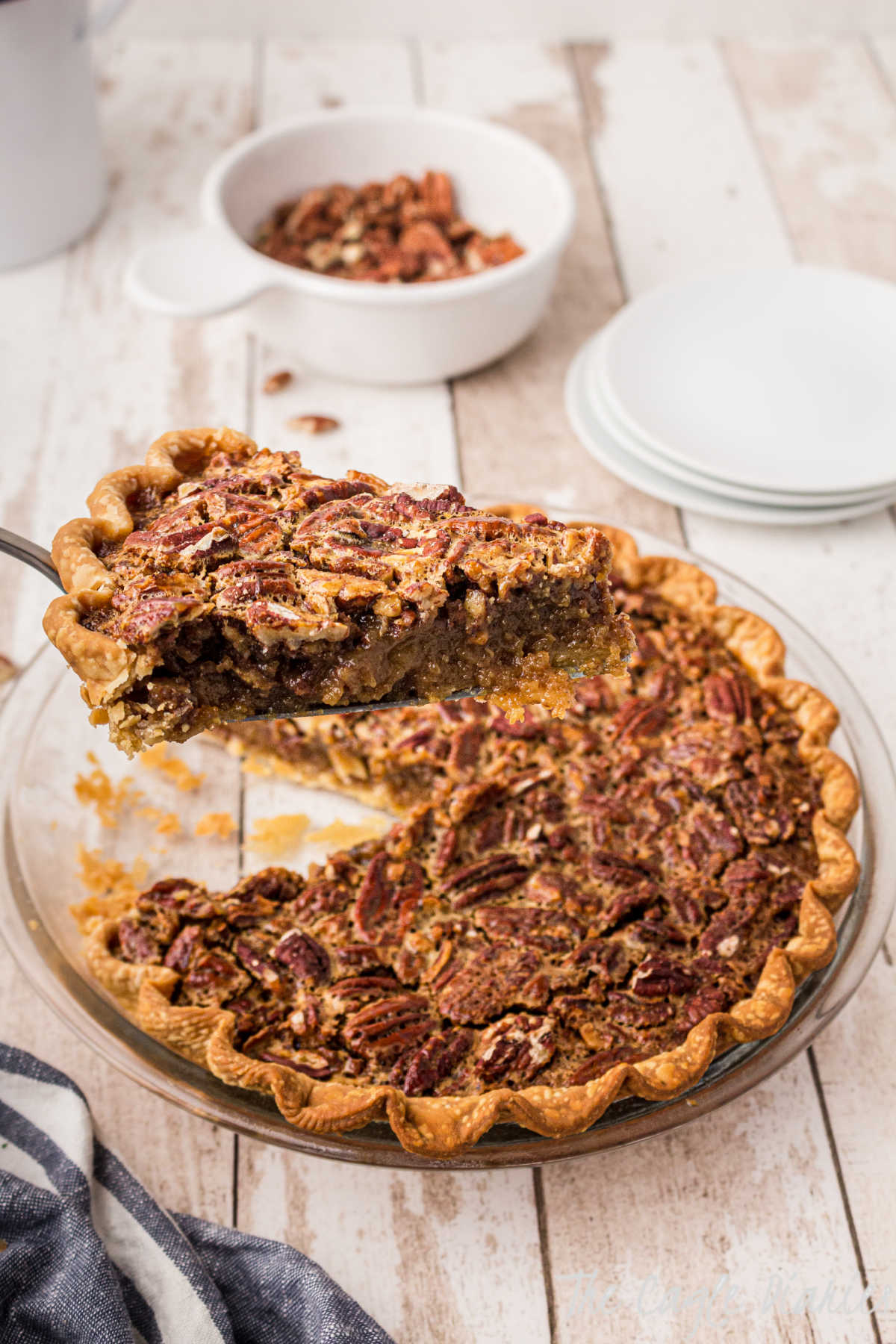 a dish with pecan pie with a slice being taken out