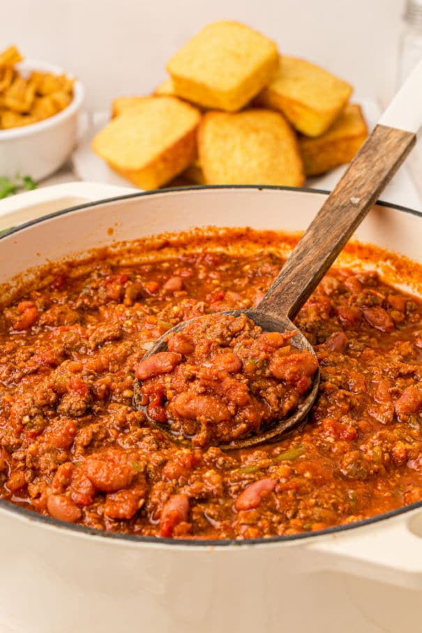 a pot of venison chili with a spoon digging in
