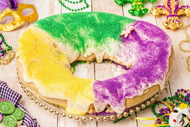 round or oval bread with icing on top coated with purple green and yellow sugar sand - king cake