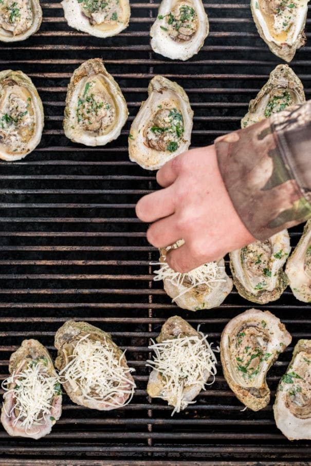 sprinkling parmesan onto oysters