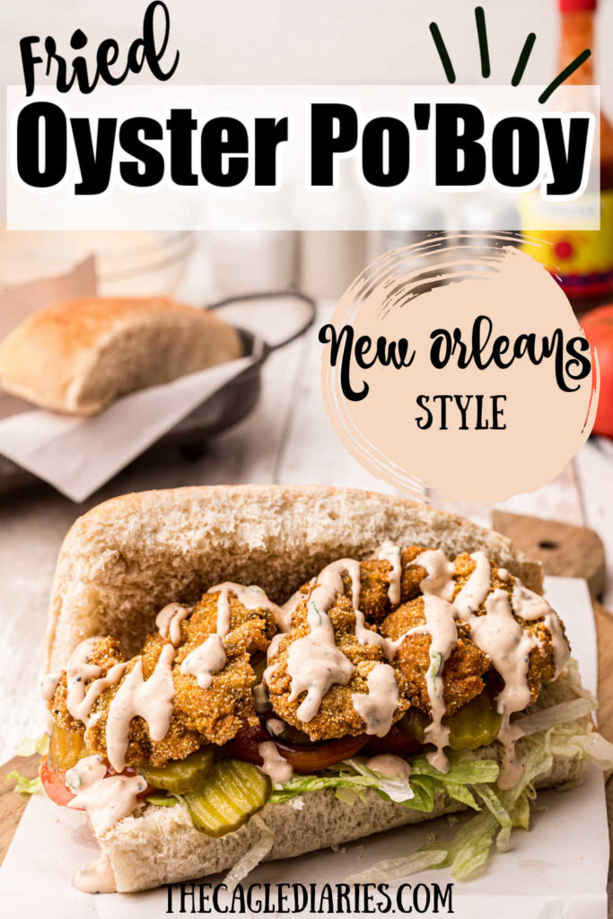 picture of fried oysters on a bun (oyster po'boy) on top of lettuce tomatoes and pickle slices.  Drizzled with a remoulade sauce.