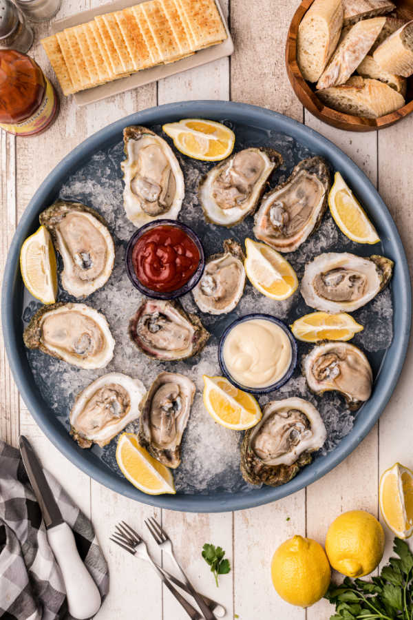A tray of raw oysters on ice with lemon wedges and cocktail and horseradish sauce