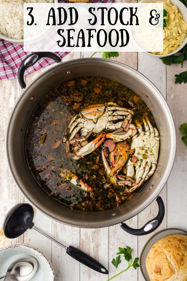 all ingredients simmering in a pot with crabs lying at the top