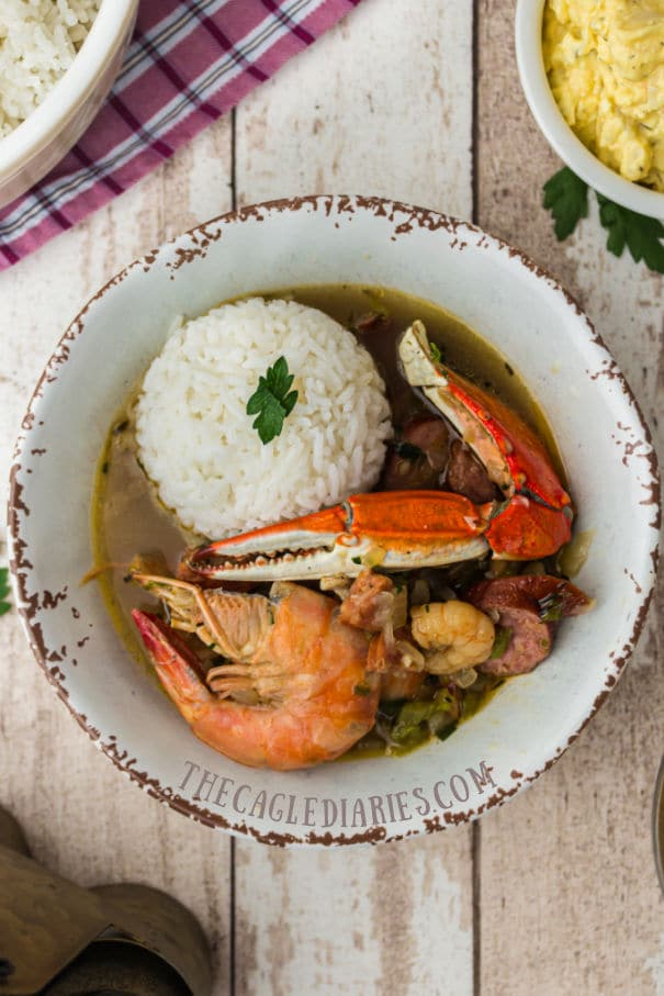 dished out bowl of seafood gumbo with a crab arm, shrimp, sausage and a mound of white rice