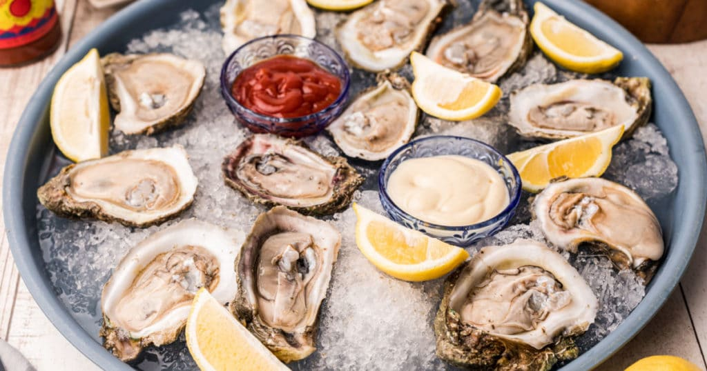 A tray with ice and shucked oysters on the half shell with lemons and dip