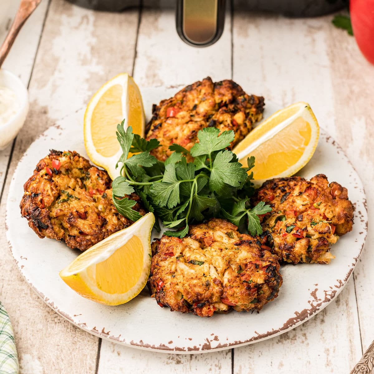 a plate of air fryer crab cakes with lemon wedges