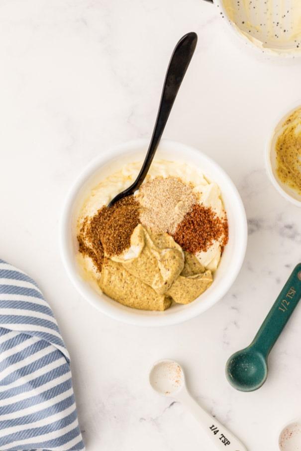 A bowl of mustard, mayo and seasonings waiting to be stirred