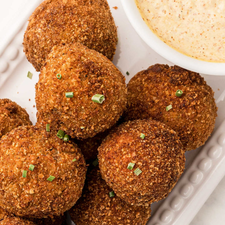 close up of boudin balls with a hint of the mustard cream sauce peeking in, sprinkled with green onions on top