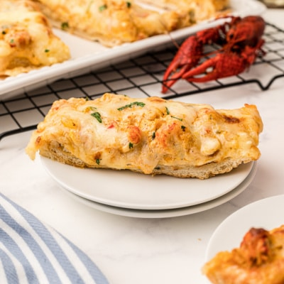 Slice of crawfish bread on a plate with a cooked crawfish sitting behind