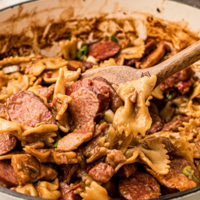 Close up of a pot of pastalaya with bow tie noodles and sausages with a spoon digging in