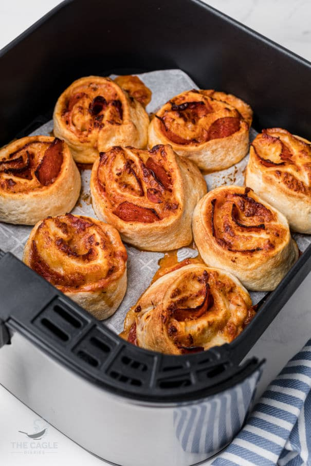 close up of homemade pizza rolls in an air fryer basket
