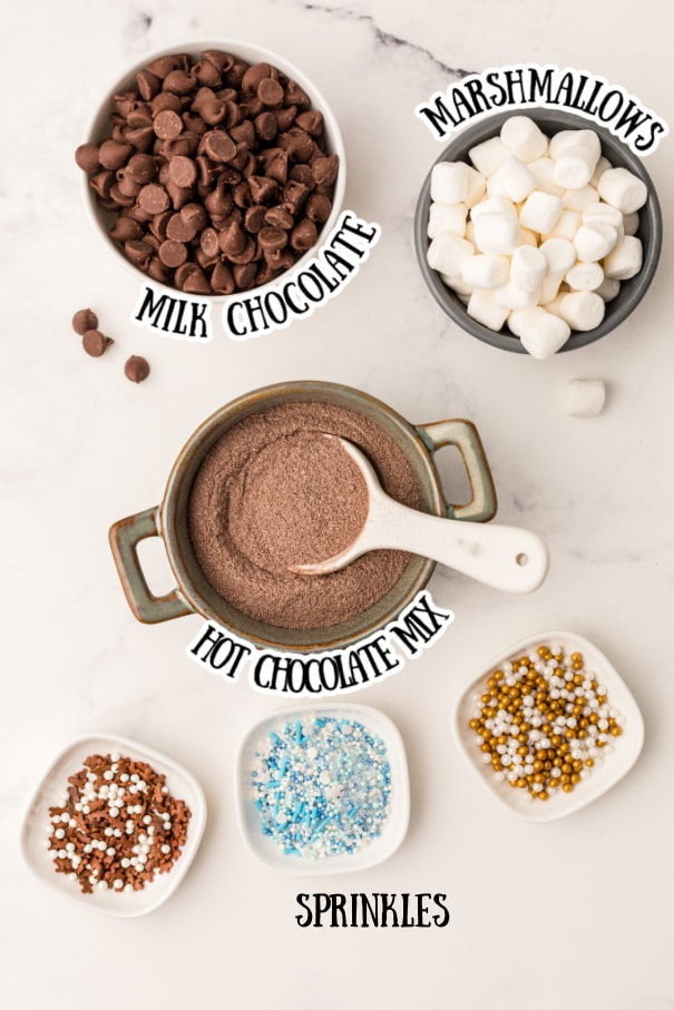hot chocolate bombs ingredients - a bowl of milk chocolate a bowl of marshmallows a bowl of hot chocolate mix and 3 bowls of sprinkles