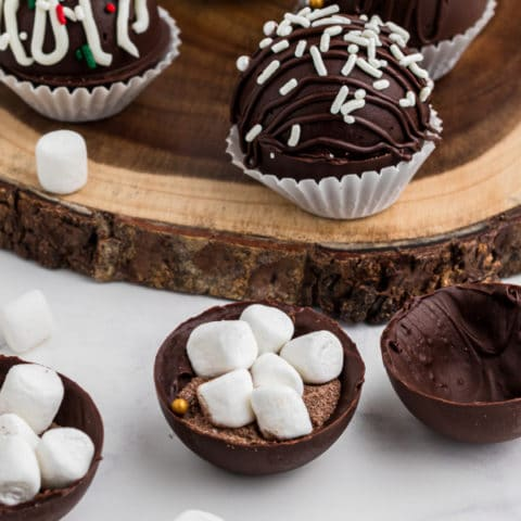 piece of wood in the background with some hot chocolate bombs sitting in cupcake liners. There's two spheres open showing the inside contents of hot chocolate mix and marshmallows
