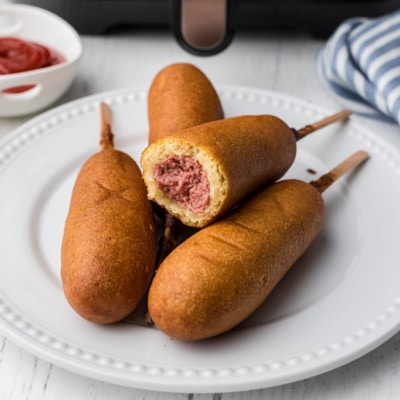 a plate full of corn dogs with a bite taken out of one of them