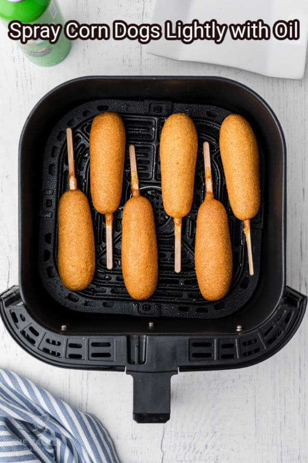 air fryer basket with corn dogs lined up waiting to be cooked
