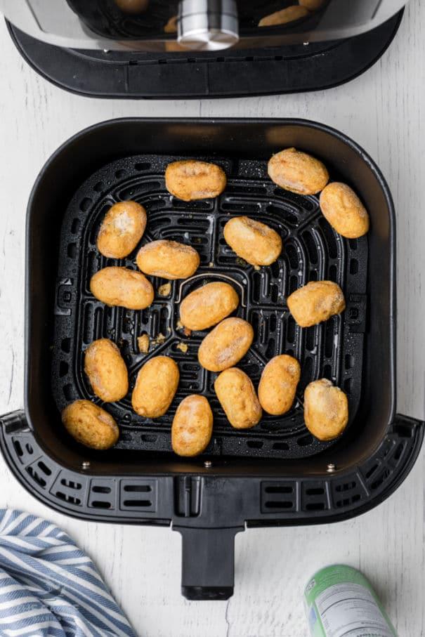 mini corn dogs in an air fryer basket