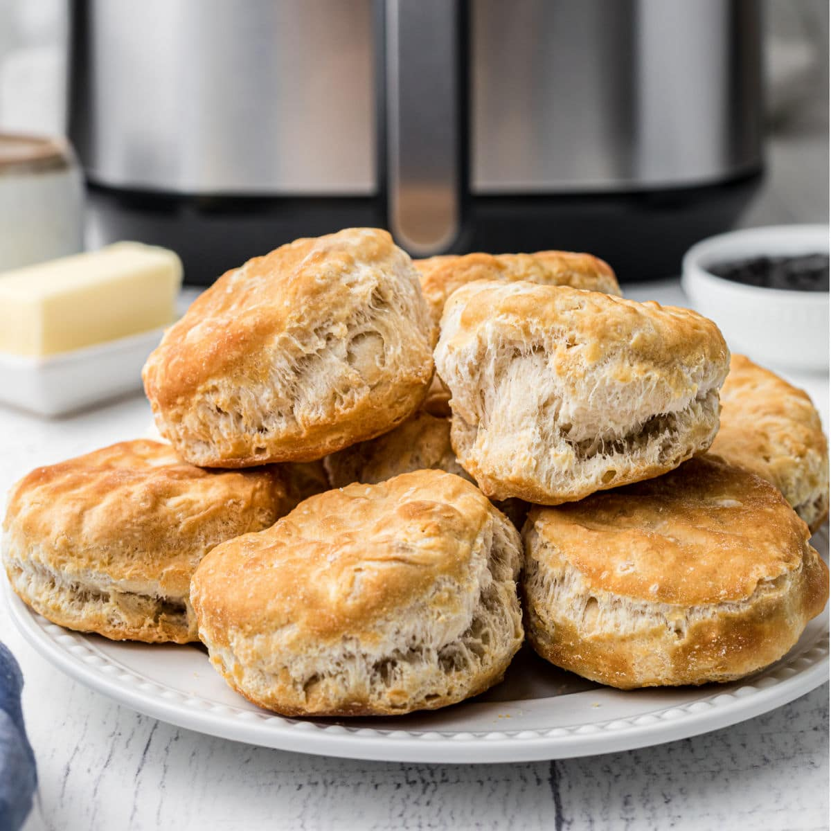 a plate of biscuits piled high, in front of an air fryer