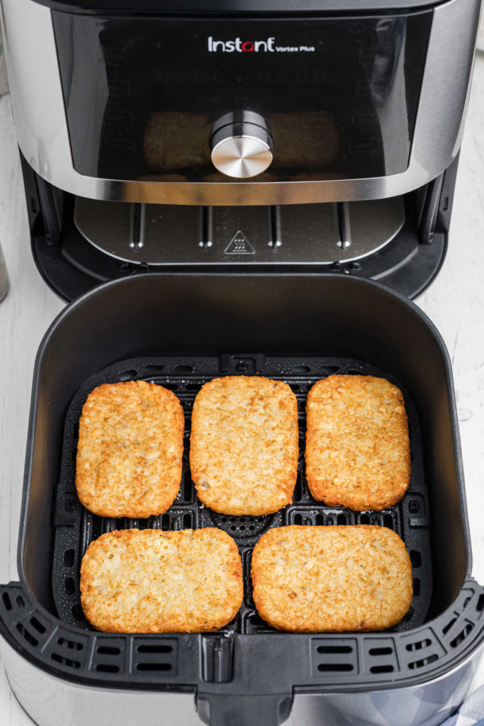 an open air fryer showing 5 hash browns cooked