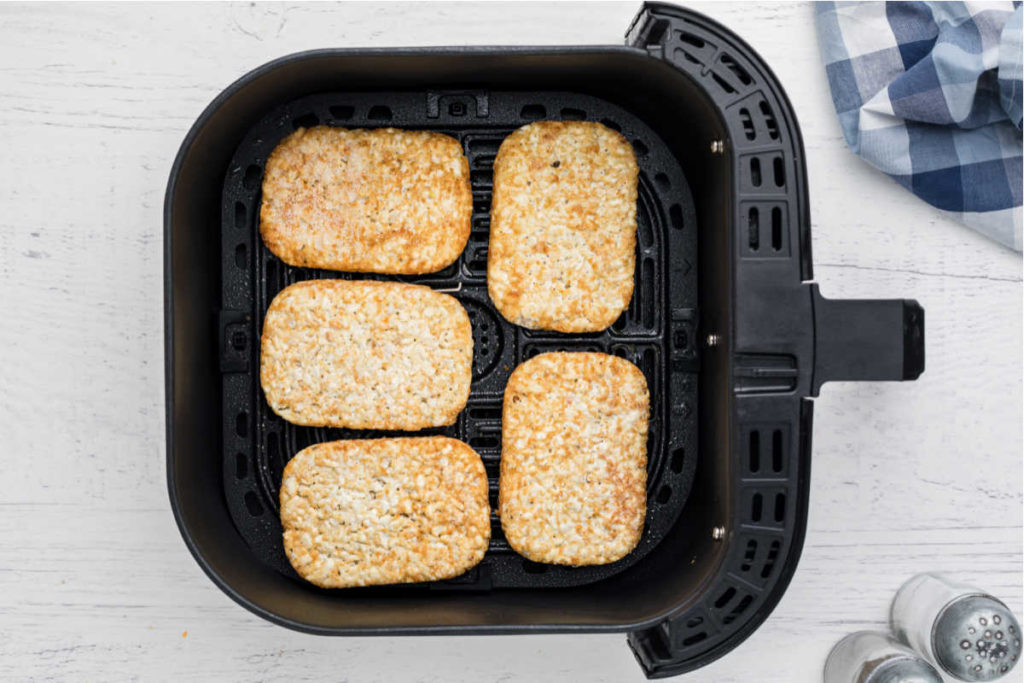 air fryer basket with hash browns lined up