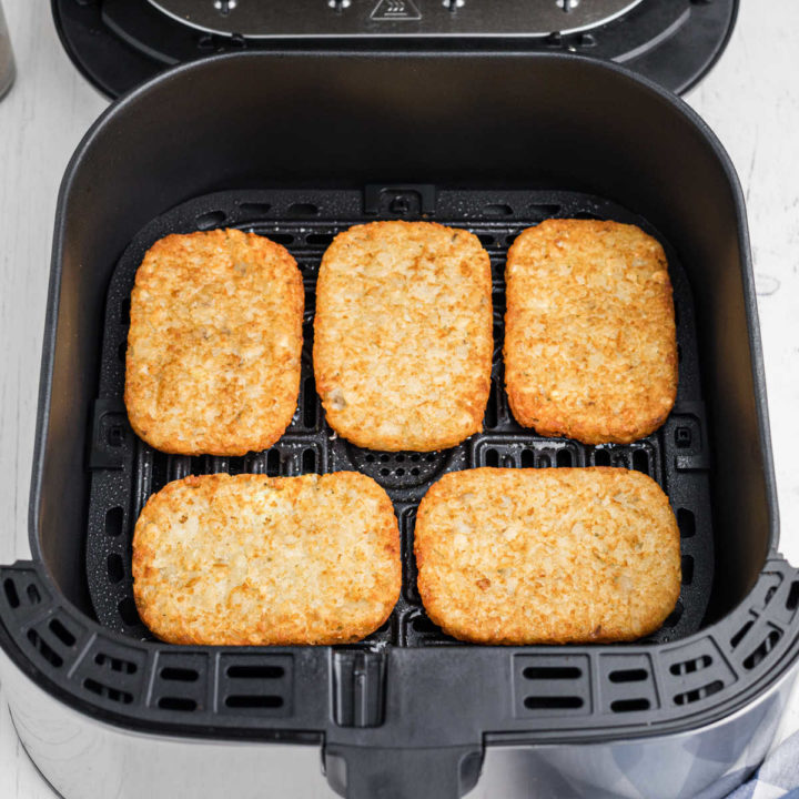an air fryer basket with 5 hash brown patties lined up