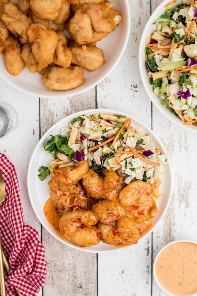 plate full of battered shrimp (tempura like) with a sweet chili sauce drizzled on top with a side salad in the background