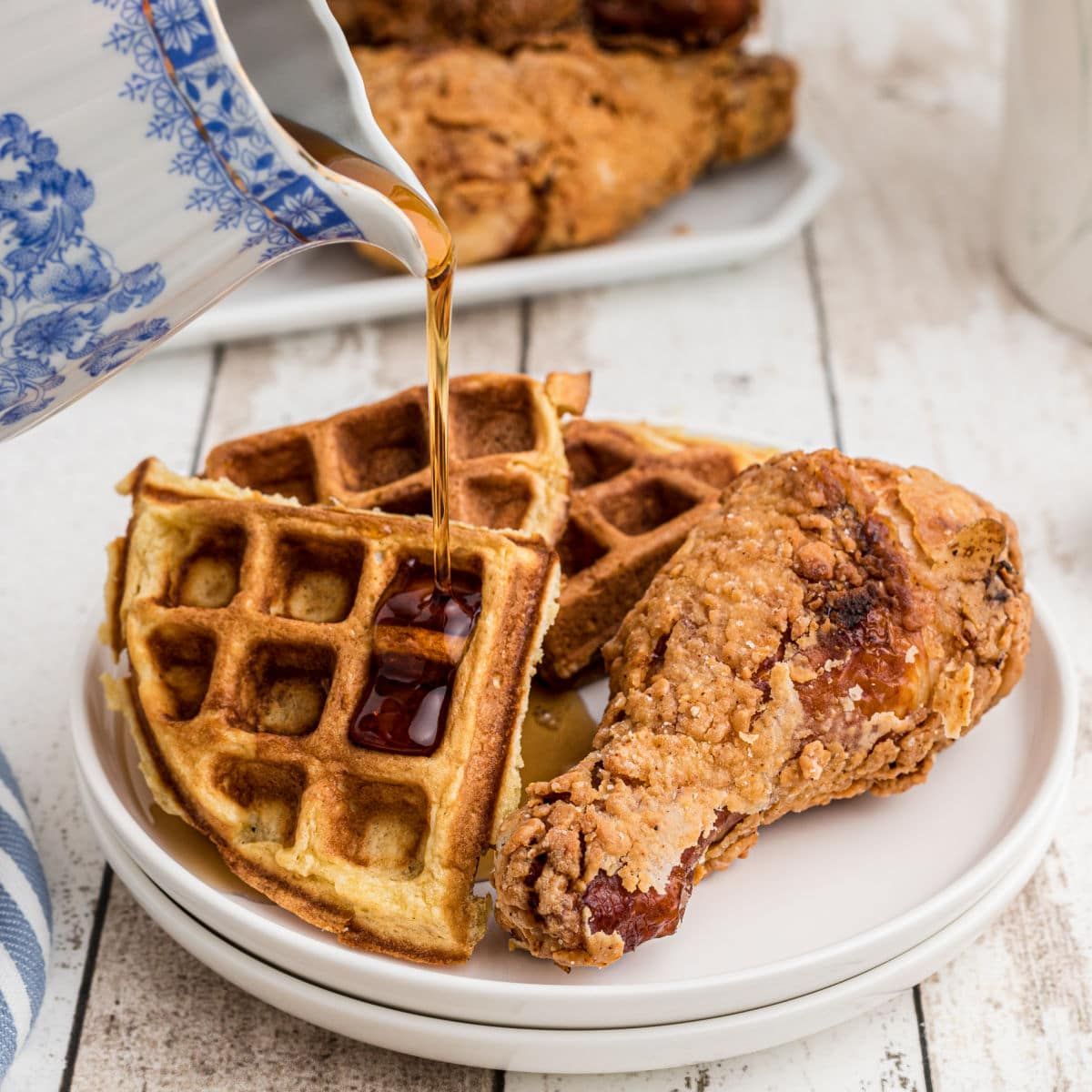 plate of fried chicken with waffles on the side with syrup being poured over the top