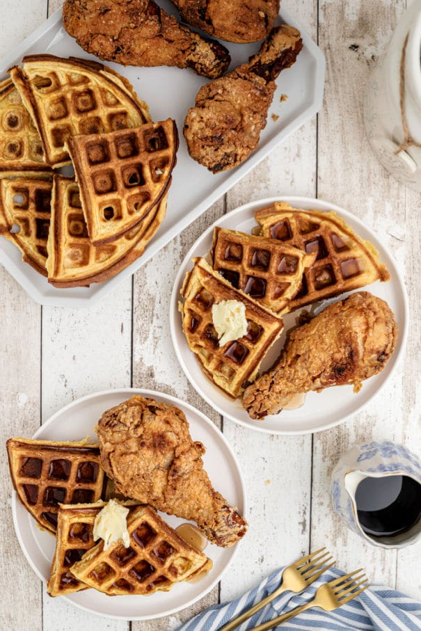 looking down on a plate with a fried chicken drumstick and some waffles on the side that have butter and syrup
