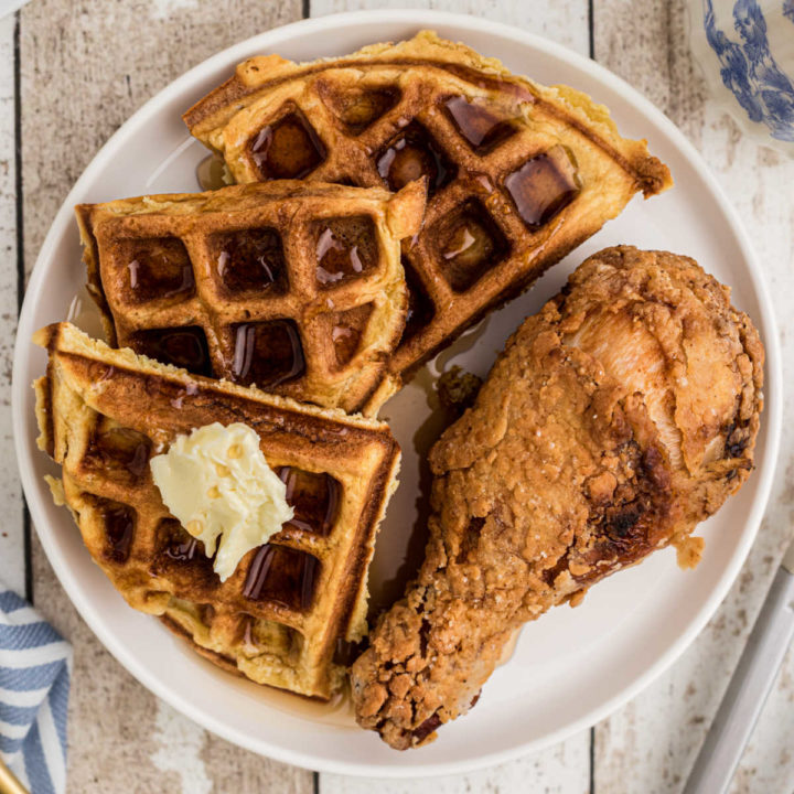 plate with a fried chicken drumstick and a side of waffles with syrup and butter